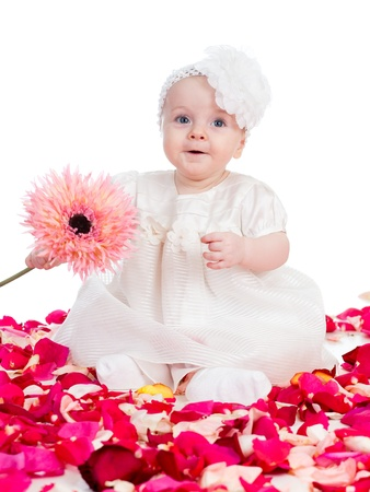 happy baby girl with flower sitting among rose petals photo