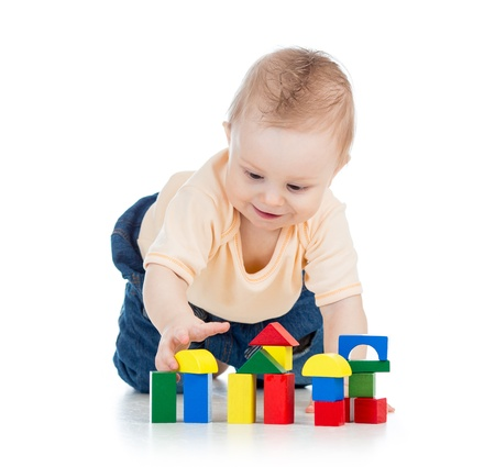 little kid boy playing with building blocks photo