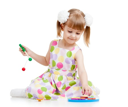 kid girl playing with toys, isolated over white photo