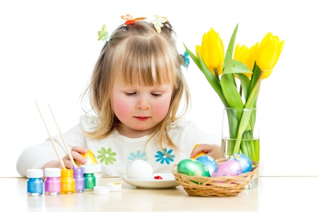 cute smiling baby girl painting Easter eggs isolated on white background photo