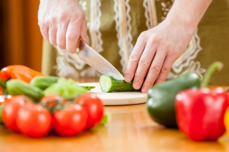 Preparing actions for vegetable salad on kitchen table  Focus on cutting cucumber Stock Photo - 17994566