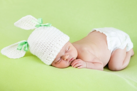 newborn baby girl: Funny sleeping newborn baby girl over green background