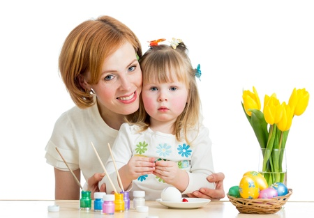 mother and kid girl paint easter eggs isolated on white photo