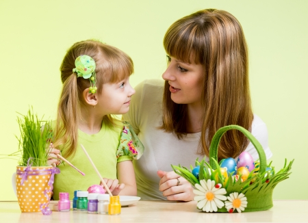 mother and child girl paint easter eggs over green background photo