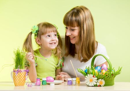 mother with child girl play and paint easter eggs photo
