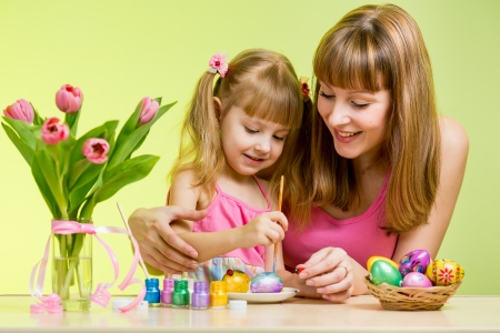 mother and daughter child painting easter eggs photo