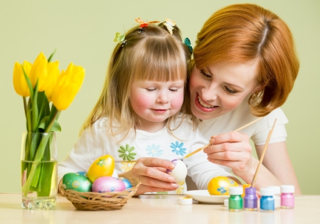 happy mother teaches daughter to paint easter eggs photo