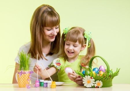 mother and child girl paint easter eggs over green background Stock Photo - 18062285