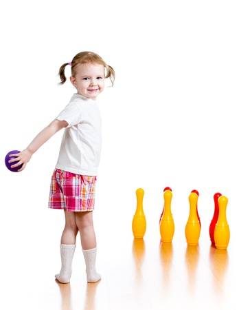 Kid girl throwing ball to knock down toy bowling pins  Focus on child  photo