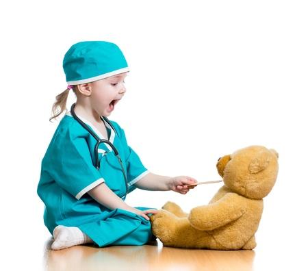 Niño adorable vestido como médico jugar con el juguete sobre blanco