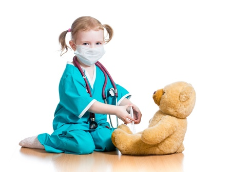 child girl with clothes of doctor playing with toy photo