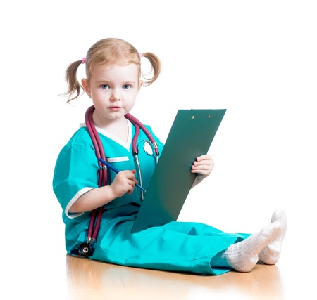Child girl uniformed as doctor writing to clipboard isolated on white photo