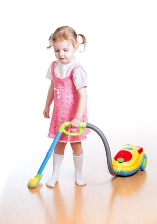 kid girl playing and cleaning room with toy vacuum cleaner photo