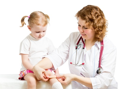 Girl with scratched knee  Doctor curing kid isolated on white  photo
