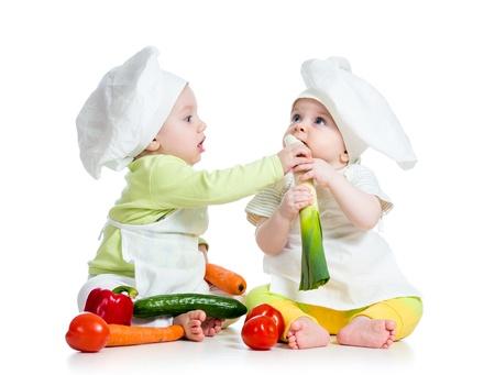 ni�os comiendo: ni�os chico y una chica que llevaba un sombrero de chef con verduras alimentos saludables