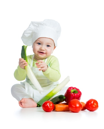 baby boy wearing a chef hat with healthy  food vegetables photo