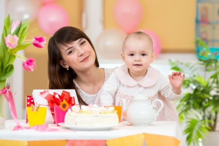 Little girl and mother celebrate birthday holiday  Focus at baby  photo