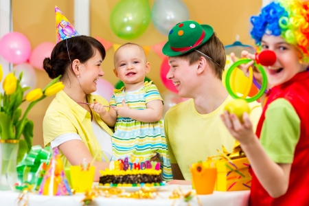 balloons party: baby girl celebrating first birthday with parents and clown