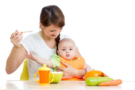 baby sitting: young mother spoon feeding her baby girl isolated on white Stock Photo