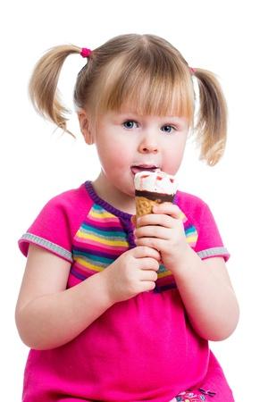 eating ice cream: alegre ni�a ni�o comiendo un helado en estudio aislado