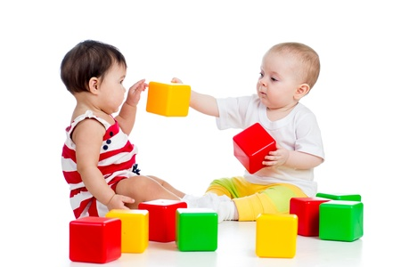 kindergarten toys: two babies or kids playing together with color toys Stock Photo