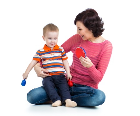 Mother and baby boy having fun with musical toys  Isolated on white background Stock Photo - 18498446