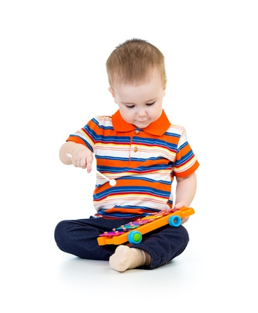 funny kd boy playing with musical toys Stock Photo - 18498462