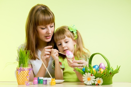 mother and child girl paint easter eggs over green background Stock Photo - 18498421