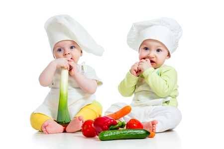 leek: babies boy and girl wearing a chef hat with healthy  food vegetables Stock Photo