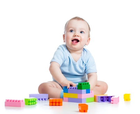 babies playing: kid boy playing with construction set over white background