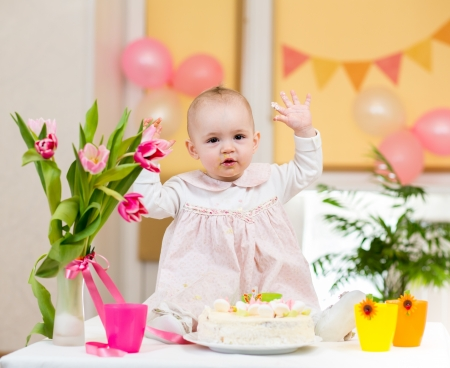 baby girl celebrating first birthday and eating cake photo