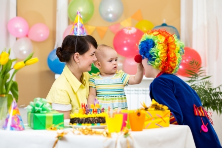 baby girl celebrating first birthday with parents and clown photo