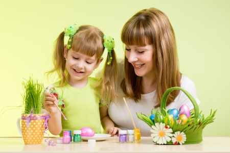 mother and child girl paint easter eggs over green background Stock Photo - 18571560