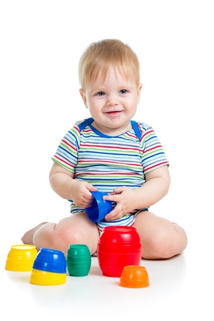 Cute baby boy playing with toys isolated over white photo