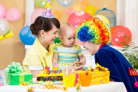 baby girl celebrating first birthday with clown photo