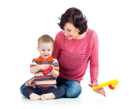 Mother and baby boy having fun with musical toys  Isolated on white background photo