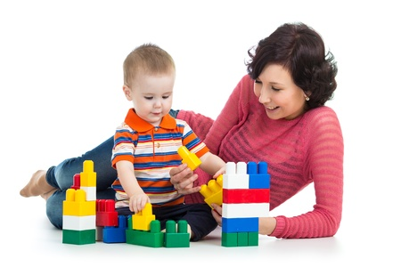 baby boy and mother play together with construction set toy photo