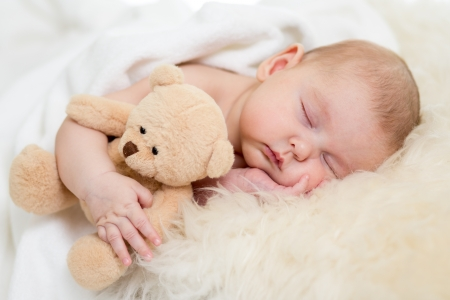 bebes: bebé recién nacido duerme en la cama de pieles Foto de archivo