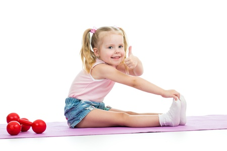 Child girl doing exercises and showing thumb up photo