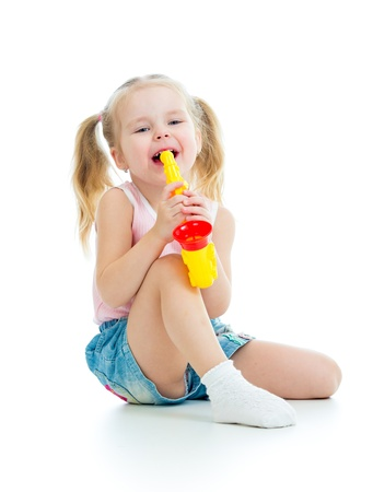 Funny baby girl playing with musical toy  Isolated on white background photo