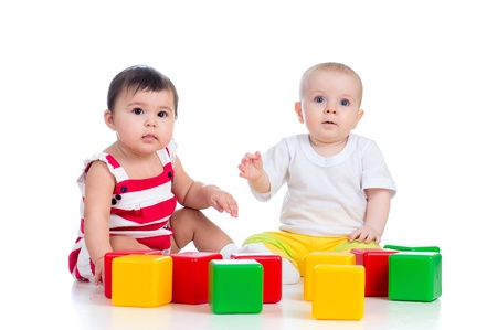 baby blocks: two babies or kids playing together with color toys Stock Photo