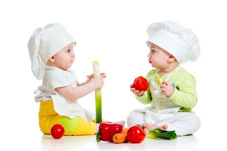 건강에 좋은 음식 야채와 함께 요리사 모자를 착용하는 아기 소년과 소녀