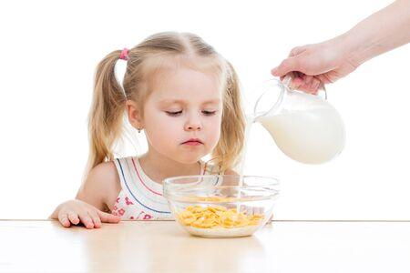 corn flakes: kid girl eating corn flakes with milk over white