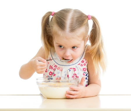 corn flakes: child girl eating corn flakes with milk over white