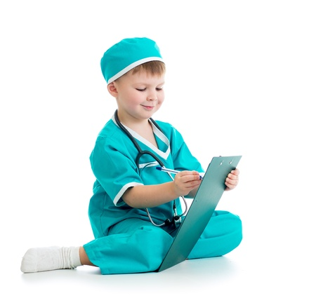 child s: Child boy uniformed as doctor writing to clipboard isolated on white