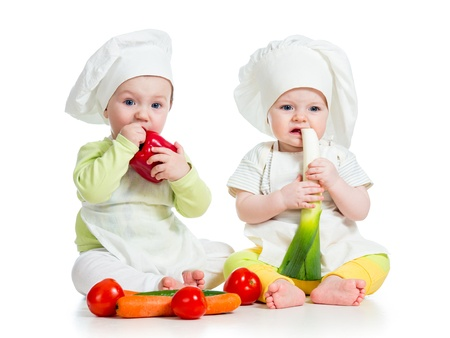 babies boy and girl wearing a chef hat with healthy  food vegetables photo