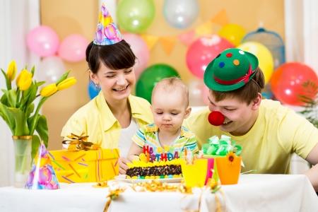 family celebrating first birthday of baby girl photo