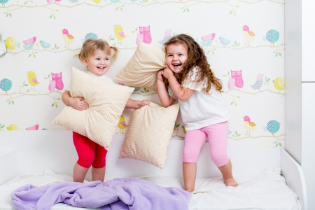 children sisters playing in bedroom photo