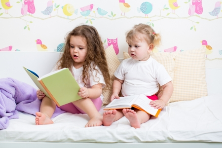 kids sisters read a book in bed Stock Photo - 18963479