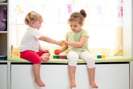 two kids sisters play together indoors Stock Photo - 18963469